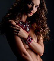 Chic. Beautiful naked woman posing in jewelry