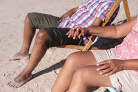 Mid section of senior african american couple holding hands while sitting on deck chairs at the beac