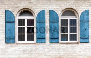 Fenster mit Fensterladen aus Holz an einem alten Gebaeude