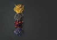 Top view of floral herbs - dried marigold, lavender, rose and cornflower petals as ingredients for cooking