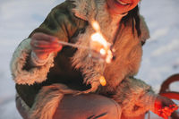 happy woman roasting frying sweet marshmallow over the camp fire in winter forest