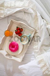 White tray with tasty breakfast to eat in bed