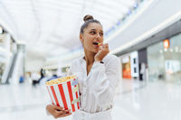 young cute woman holding popcorn in the mall background