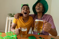 Laughing mixed race gay male couple wearing st patrick's day costumes and holding glasses of beer