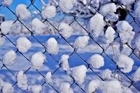 Maschendrahtzaun mit Schnee bedeckt