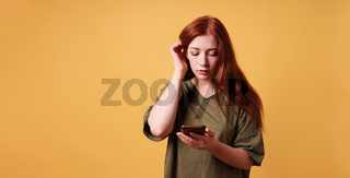 young woman reading text message on smartphone or mobile phone