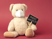 German Hold on, Teddy bear with protective mask holds sign