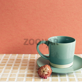 Mint coffee cup with dry flower on mosaic tile table. red wall background