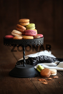 Cake stand with macaroons on dark wood background