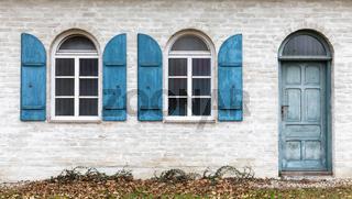 Tuer und Fenster mit Fensterladen aus Holz an einem alten Gebaeude