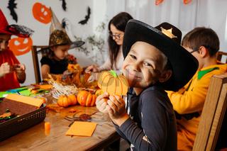 Cute boy in cowboy hat demonstrates his handmade paper pumpkin
