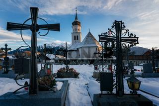 Village church during sunset seen through tomb crosses at snow covered graveyard, Wildermieming, Tirol, Austria