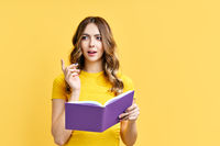 Dreamy positive girl rest with book on yellow background with copy space