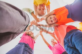 team of boys and girls are stacking hands together