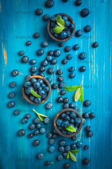 Organic blueberries on blue wooden background.