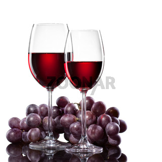 Red wine in glasses with grape isolated on white