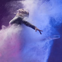 Girl in pointe shoe in dust cloud and color light