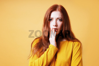 worried frightened young woman covering her mouth with her hand