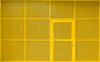 modern yellow building exterior with metallic facade and door