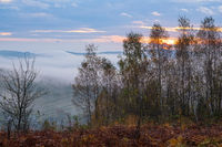 Cloudy and foggy autumn mountain sunrise scene. Peaceful picturesque traveling, seasonal, nature and countryside beauty concept scene.