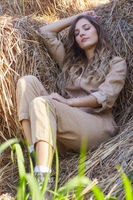 Young blonde woman in a beige jumpsuit is sleeping on the rolls of hay.