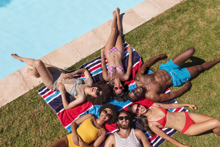 Diverse group of friends sunbathing together by pool on a sunny day