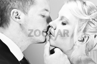 Beautiful young couple kissing in black and white