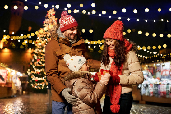 happy family with gift at christmas market in city