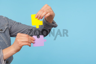 Closeup of female hands holding colorful pieces of puzzle, two jigsaw parts of one