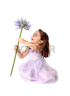 Little girl spinning a large stemmed flower with delight