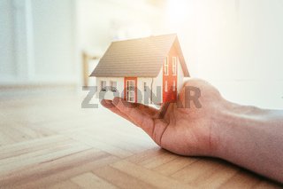 New home and house concept: Red house model indoors in male hand