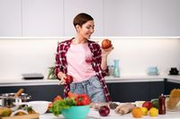 Housewife cooking apple pie standing at the kitchen wearing plaid shirt with a short hair. Holding an apple in hand happy woman dancing at kitchen with a sexy eye contact on camera