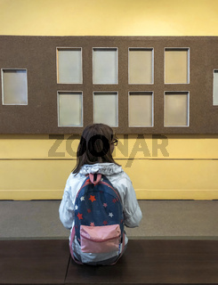Back view of teen school girl with backpack sitting on bench in museum
