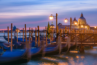 Basilica di Santa Maria della Salute and gondolas on the sea at sunrise / sunset time, Venice, Italy
