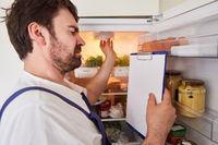 Handwerker mit Checkliste kontrolliert Kühlschrank