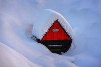 small well with name Zofka with a red house in a snowy landscape