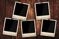 Empty instant photo frames pinned on wooden wall