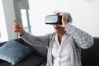 Mixed race senior woman sitting on sofa wearing vr headset touching virtual screen