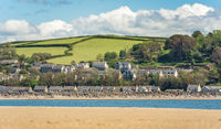 View of LLansteffan beach in southern Wales surrounded by sand, houses, and mountains