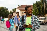 The young african student uses navigation on a smartphone