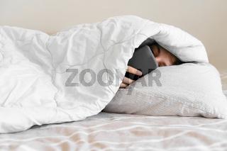 Young woman goes to sleep Phone addiction, insomnia. try to fall asleep. Sleep tracking on the phone. Circadian rhythm.