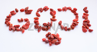 Goji Berries shaped into word 'goji' isolated on white