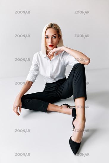 Portrait of daring trendy woman posing on white studio background. sitting on floor