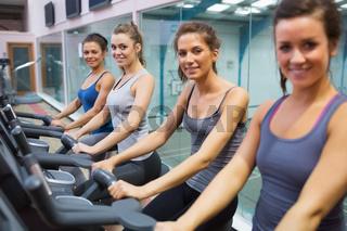 Happy women on exercise bikes