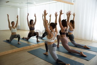 Group of young sporty women in yoga studio, practicing yoga pose in front of the mirror. Healthy active lifestyle, working out indoors in gym