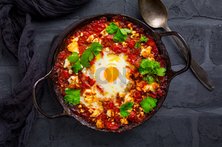 Shakshuka -  dish of eggs poached in a tomato sauce with Feta cheese and coriander in baking pan