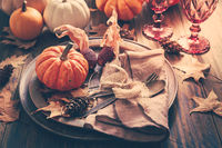 Place setting for Thanksgiving with pumpkins and autumn leaves