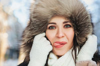 Playful female in outerwear showing tongue