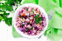 Salad with herring and beetroot in bowl on board top