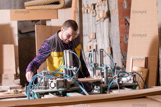 Cheerful carpenter operating woodworking machine in dusty workshop